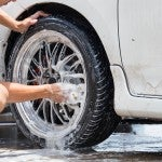 Outdoor tire car wash with sponge.