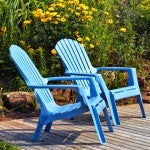 Brilliant blue plastic outdoor Adirondack chairs on the deck in a summer garden.